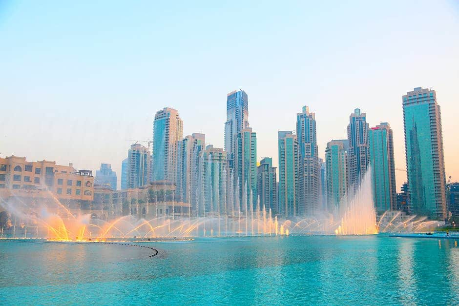 A fountain in a body of water with a city in the background