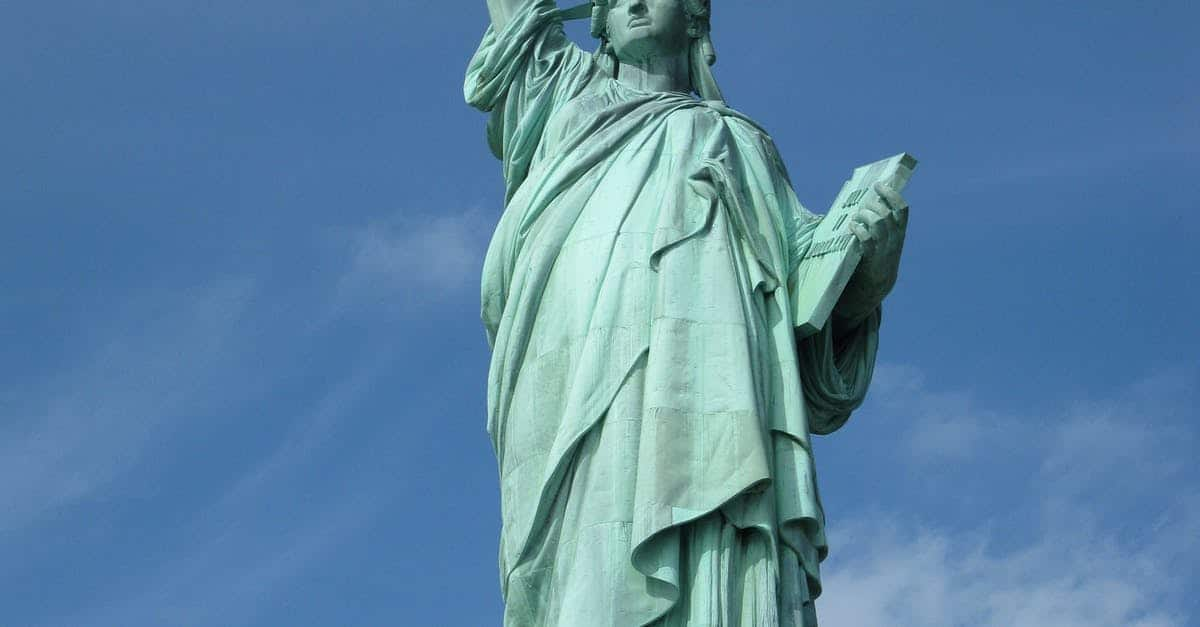 A green dress standing in front of a cloudy blue sky with Statue of Liberty in the background