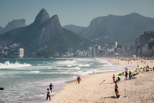 A group of people on a beach with Ipanema in the background